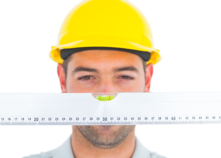 Handyman looking at spirit level over white background