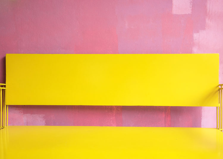 Vintage bright yellow Bench Against grunge pink painted Wall, bright summer colour