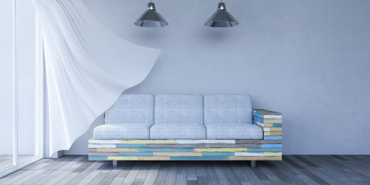 3ds rendered image of living room which have cracked concrete wall and old wooden floor and colorful old wooden sofa set, White fabric curtains being blown by wind from the sea