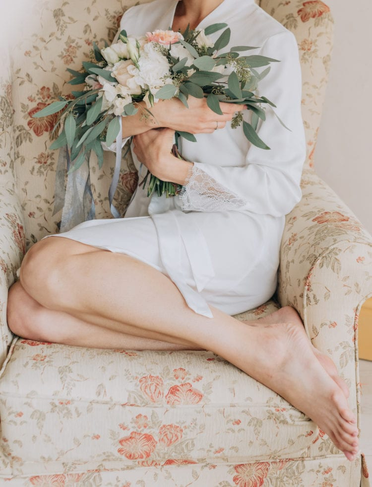 woman in a white robe sits in an armchair with a bouquet of flowers thrown legs