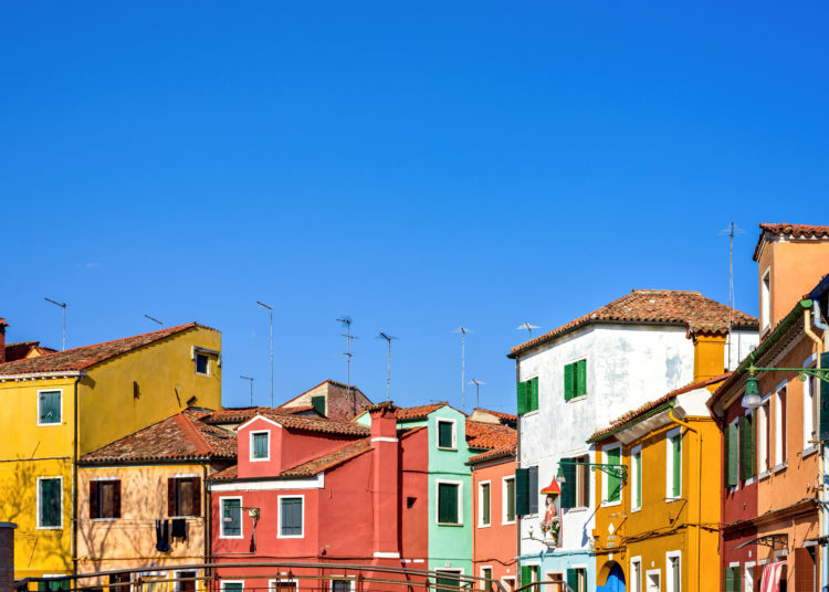 Daylight view to colorful buildings facades with chimney and antennas on rooftop. Bright blue clear sky. Negative copy space, place for text. Burano, Italy