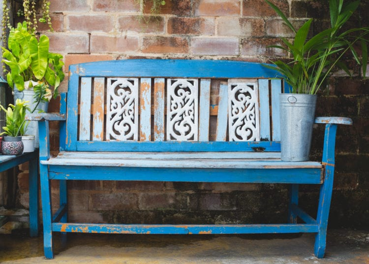 Blue wooden bench in flower garden with brick wall