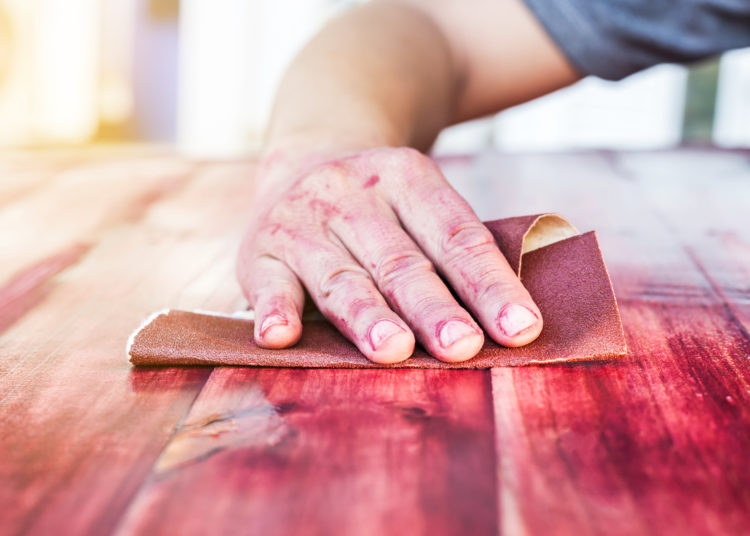 hand sanding and smoothing red wooden with sandpaper.