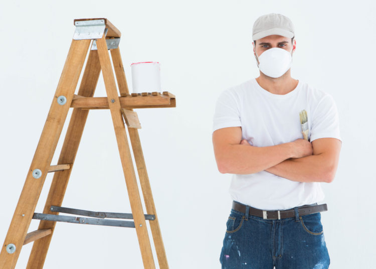 Portrait of man with paintbrush standing arms crossed by ladder on white background