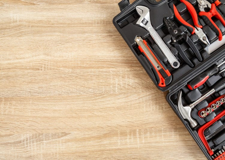 New square black tool box on wooden texture background. Top view