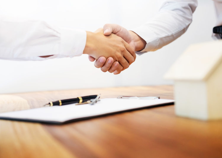 Estate agent shaking hands with customer after contract signature as successful agreement in real estate agency office. Concept of housing purchase and insurance.