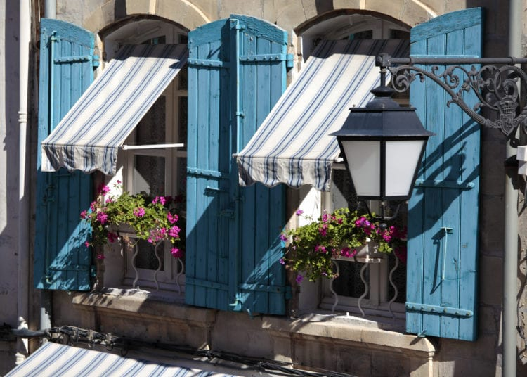 France provence style cottage windows, blue shutters and flower boxes.