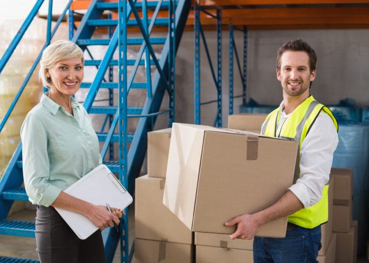 Worker holding box with manager holding clipboard in a large warehouse