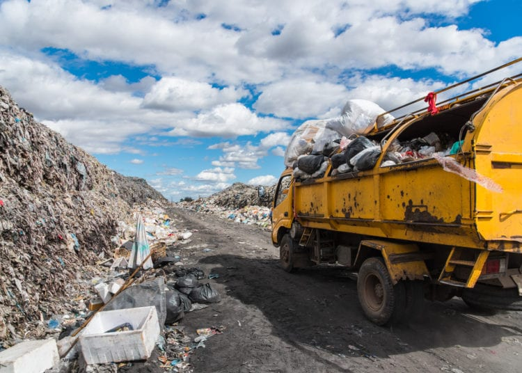Dump trucks unloading garbage over vast landfill