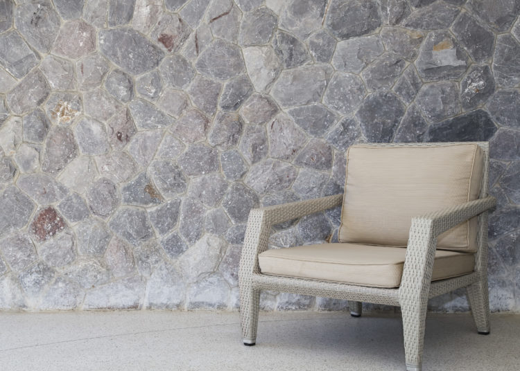 Outdoor furniture wicker chair with stone wall