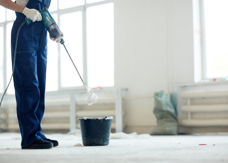 Painter in coveralls mixing whitewash in bucket