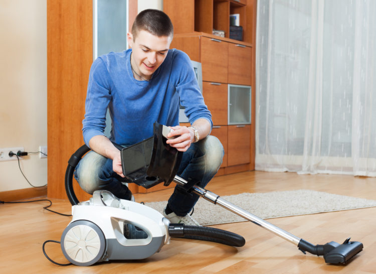 Smiling man vacuuming with vacuum cleaner on parquet floor in living room