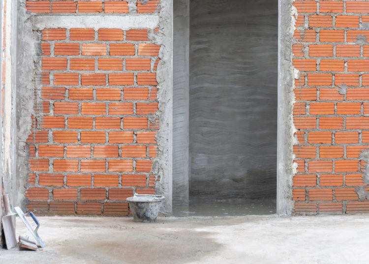 Red brick wall with doorway in residential building construction site