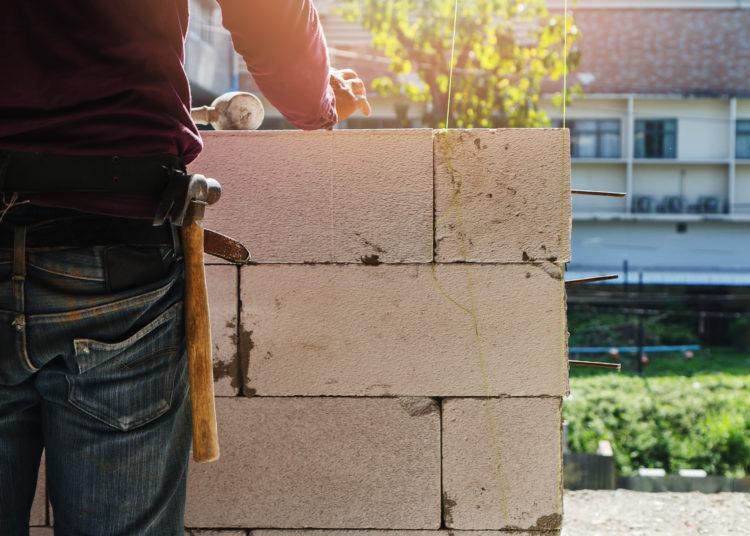 Mason worker building exterior walls, Industrial bricklayer installing bricks on construction site