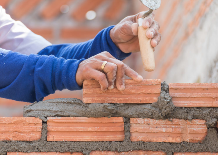 Bricklayer working in construction site of a brick wall. Bricklayer putting down another row of bricks in site