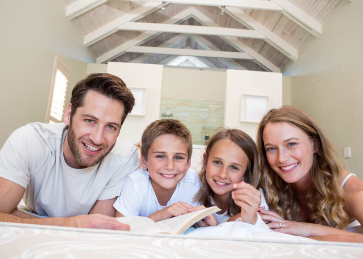 Happy family on the bed reading book at home in bedroom