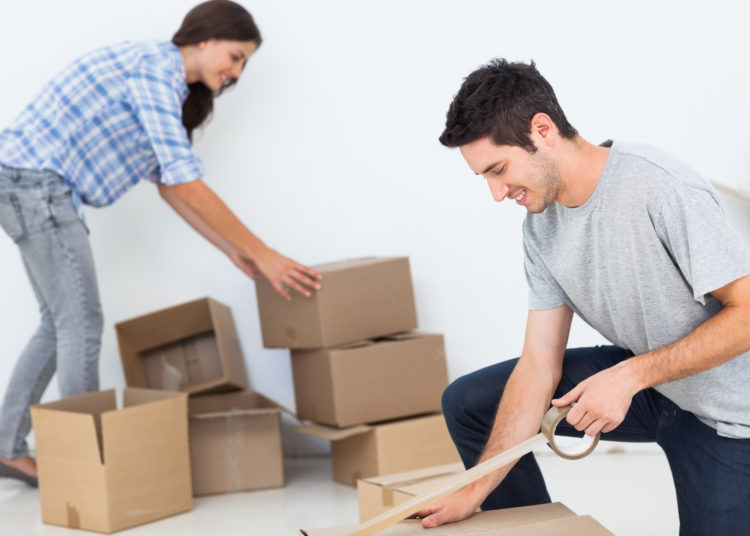 Woman and man wrapping boxes while they are moving home