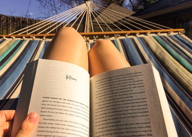 Young woman reading a book lying on hammock on the patio