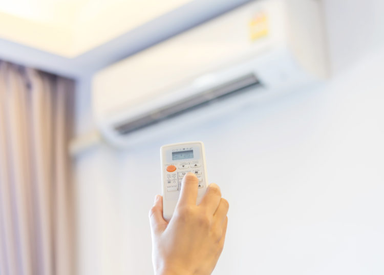 Hand hold remote control turn on air conditioner.
