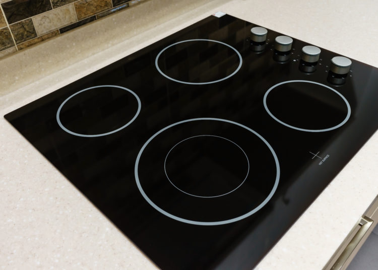 Modern black induction stove, cooker, hob or built in cooktop with ceramic top in white kitchen interior