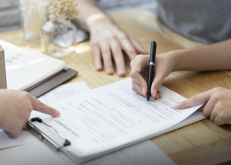 woman putting signature on document loan contract, real estate purchase, hands of woman sale represent point document to sign, contract deals success business.