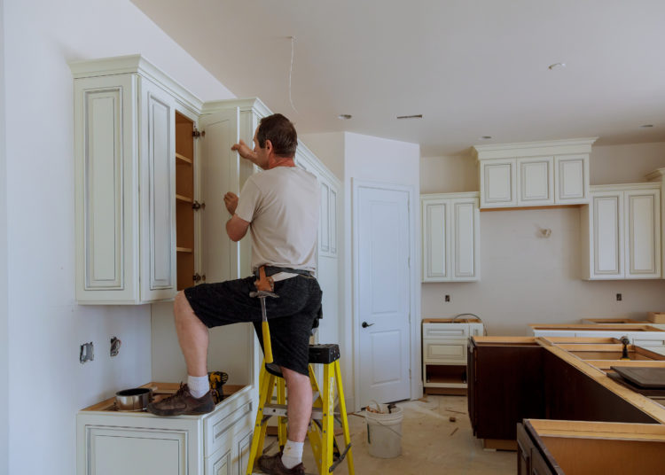 Man installing kitchen cabinets door installation of kitchen