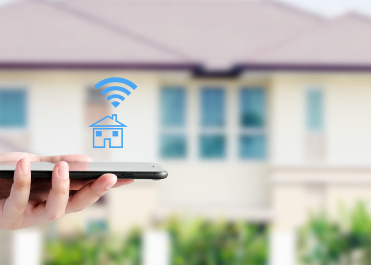 Hand using smart phone with smart home control icon over blur house background, smart home control concept