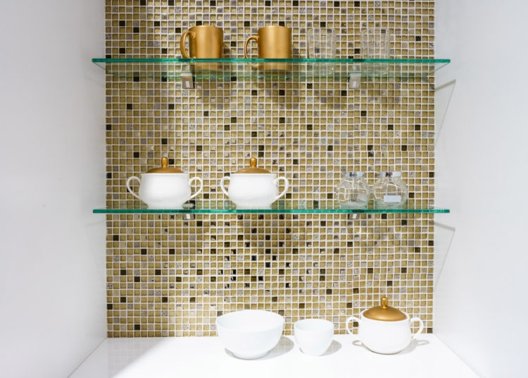 kitchen ceramic and white mug on a glass shelves in a white cabinet with colorful mosaic background.