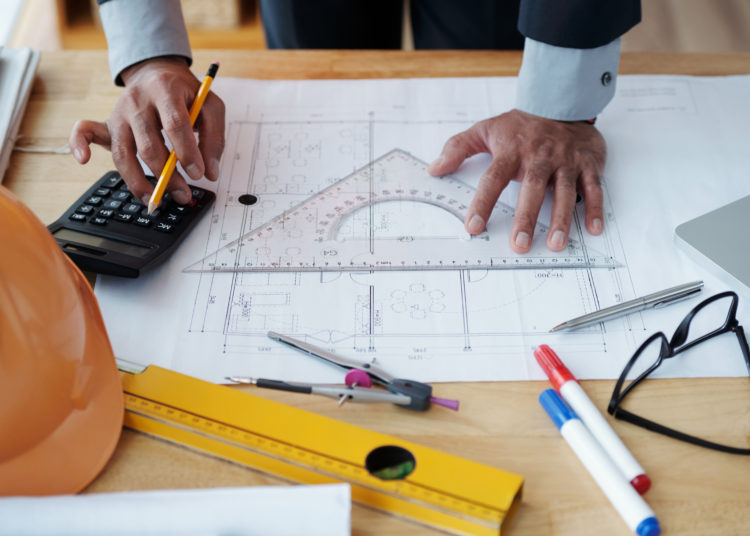 Hands of engineer checking construction plan on his table
