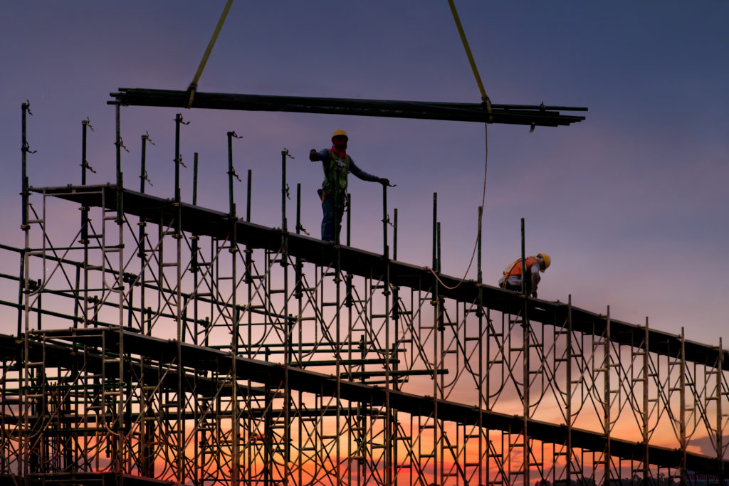 Man working on construction site with scaffold and building with